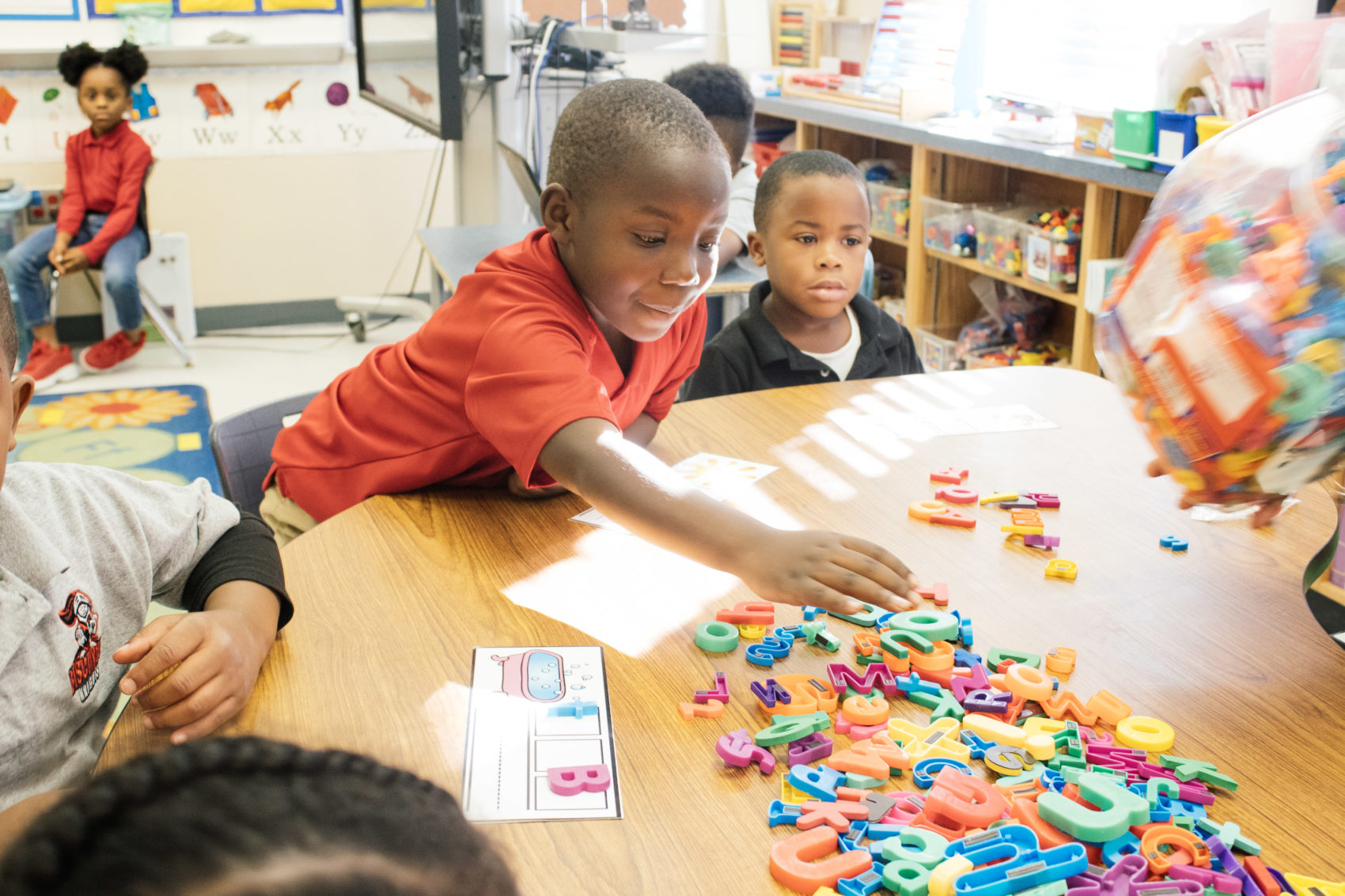 Picture of student learning to spell with colorful, plastic letters.