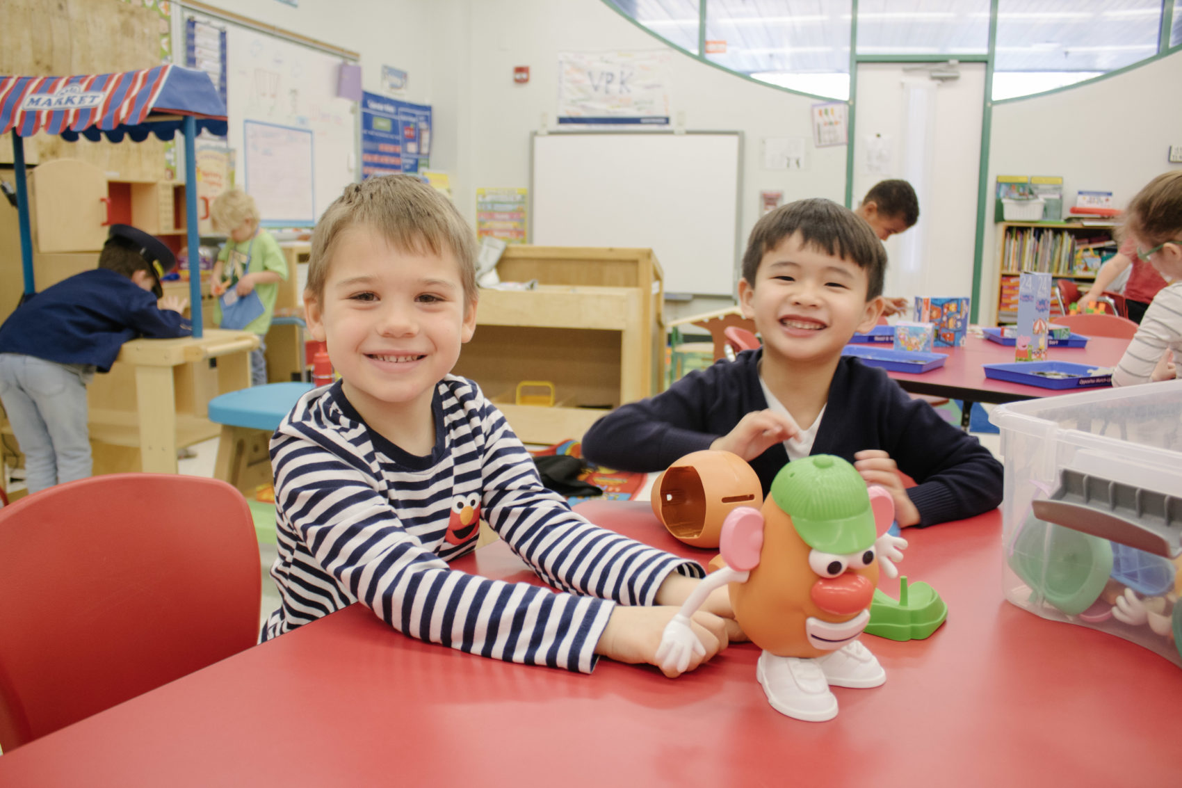 Two boys smile while playing with a Mr. Potato Head.