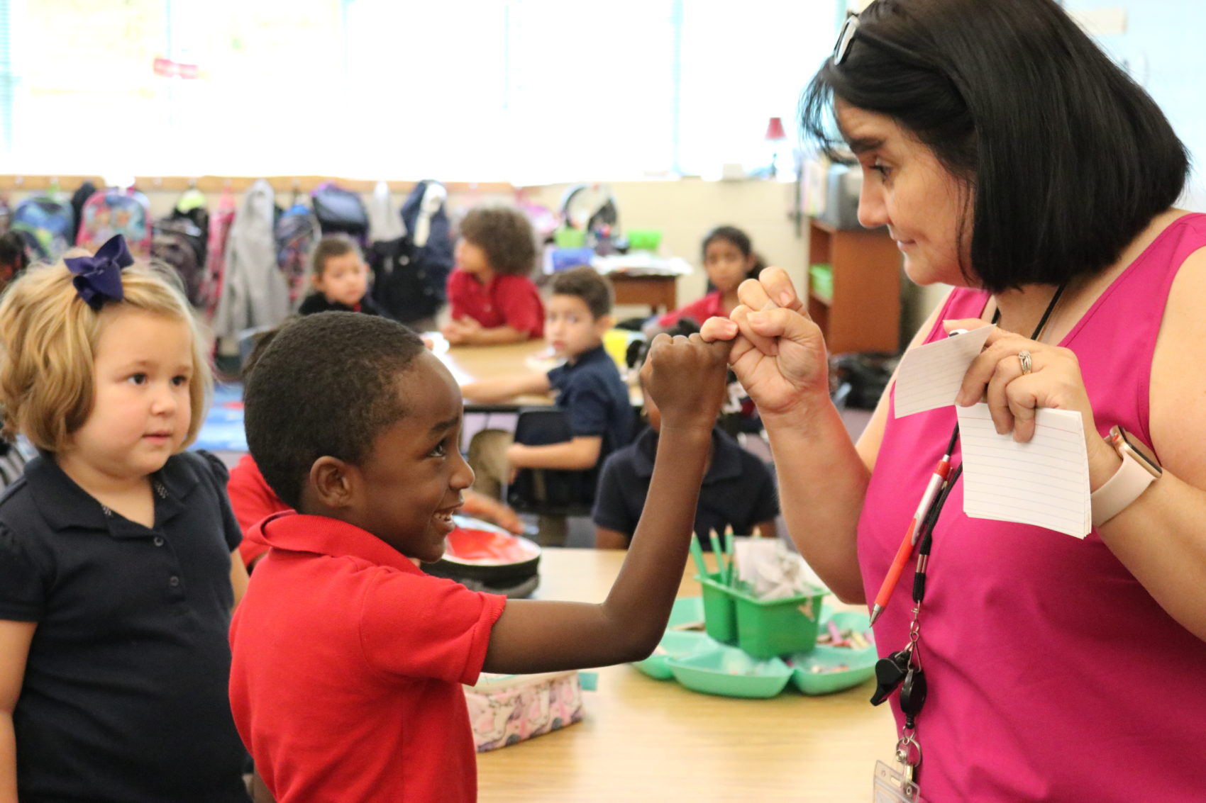 Picture of a teacher and Kindergarten student pinky swearing.