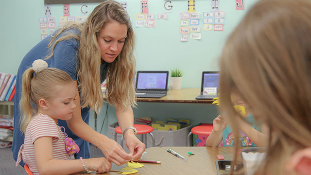 A Neptune Beach Elementary Teacher assists her young student with a paper mustache she's making.