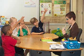 Picture of students sitting at a table with their teacher while the teacher shares a flash card.