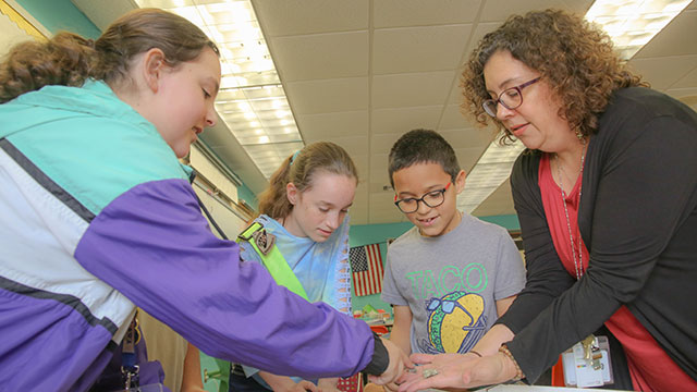 Picture of students working on a science experiment together with their teacher.
