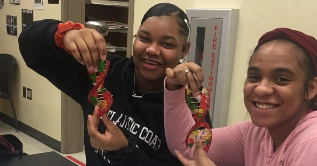 Picture of two female students showing off models of DNA made out of candy.