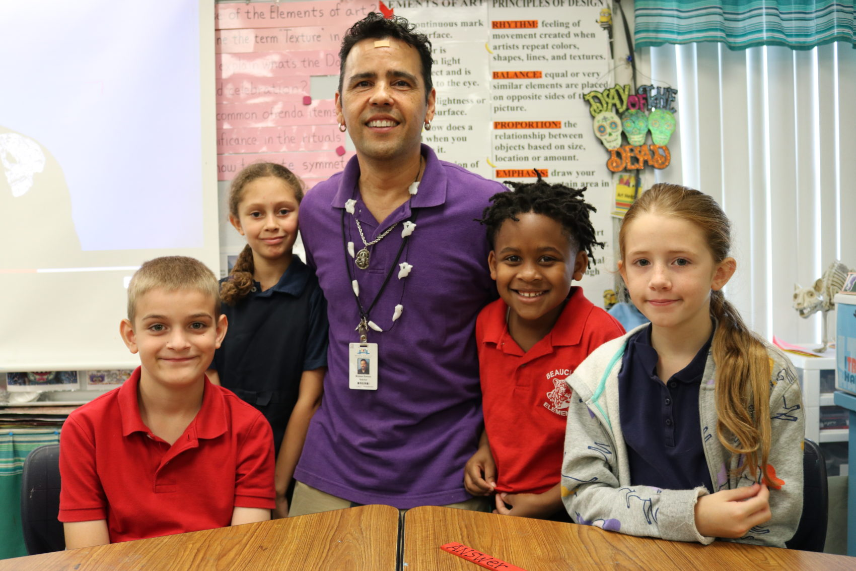 Picture of teacher with his students grouped around him.