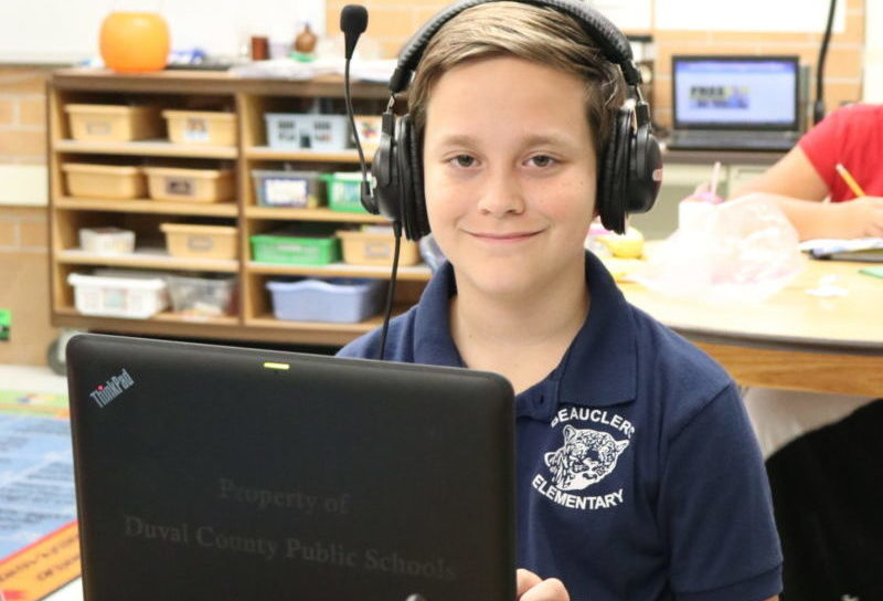 Picture of student smiling as he looks up from his computer at Beauclerc Elementary School