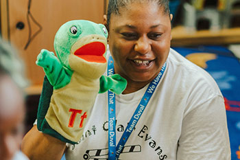 A picture of a teacher holding a puppet