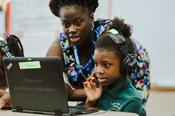 A picture of a student and teacher look at a computer together.