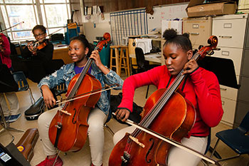 Picture of children playing string instruments.