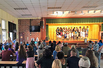 Children gather in a cafeteria to watch a chorus sing on a stage.