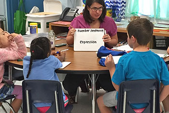 Teacher holding a sign to help students learn to read.
