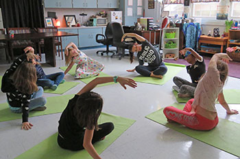 students sitting in a circle doing yoga with an instructors at Ruth Upson Elementary School in Jacksonville, FL
