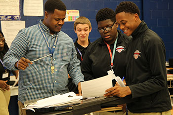 Band students discuss an assignment with a teacher at Joseph Stilwell Military Academy