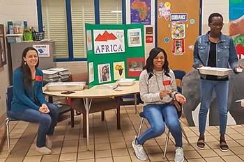 Teachers at Chimney Lakes sitting at a table in front of a display of Africa.