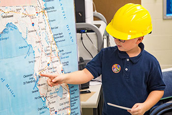 Child posing in front of a map of Florida with a hard hat on.