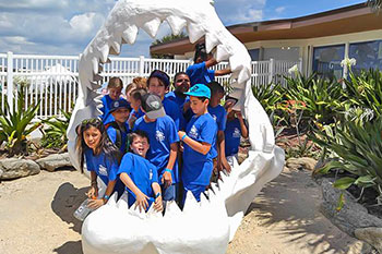 Children posing for picture inside replica of shark jaws