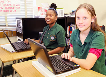 Girls learning lessons on computers at Matthew Gilbert Middle School.