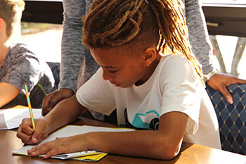 Crown Point Elementary student writes on paper at a desk.