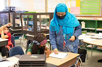 A teacher leans over a student's desk to help her with a problem.