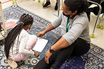 A teacher instructs student while seated on the floor.