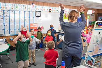 A teacher leads little VPK students in an educational dance.
